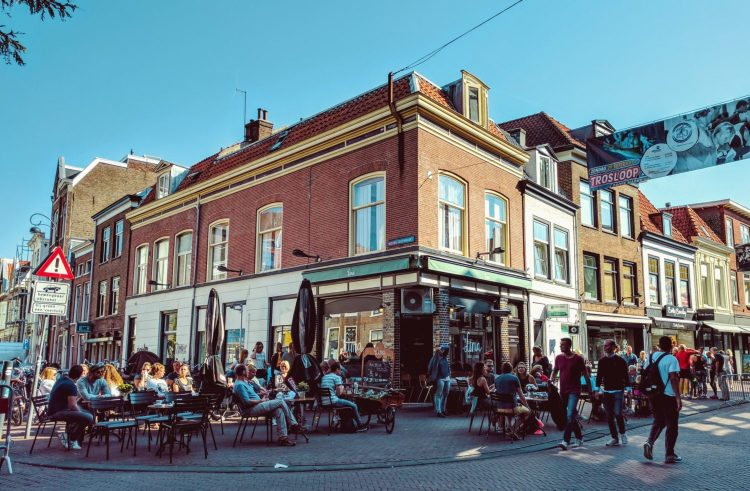 People sitting outside at a cafe on a sunny day.
