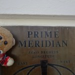 Choo posing with the sign for the Prime Meridian