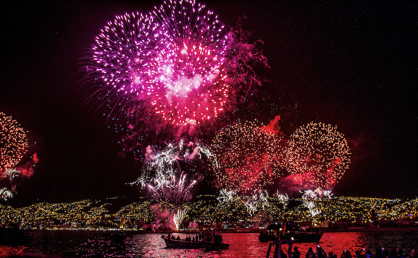 Red fireworks being watched by people in a boat on a lake.