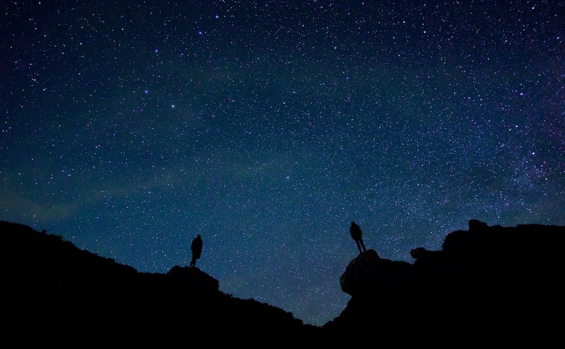 Blue stars filled sky with two people gazing from cliffside