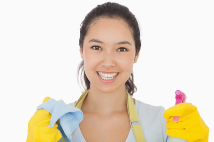 Smiling woman in rubber gloves with cloth and spray bottle