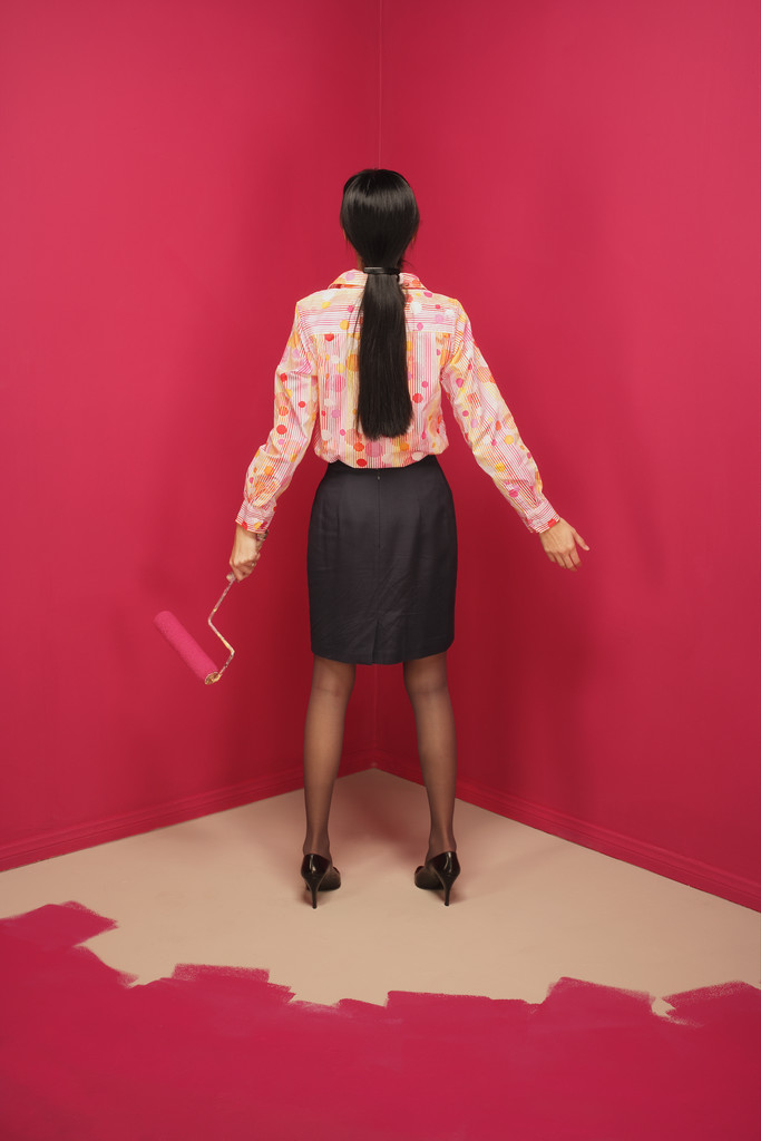 Rear view of a young woman holding a paint roller --- Image by © Royalty-Free/Corbis