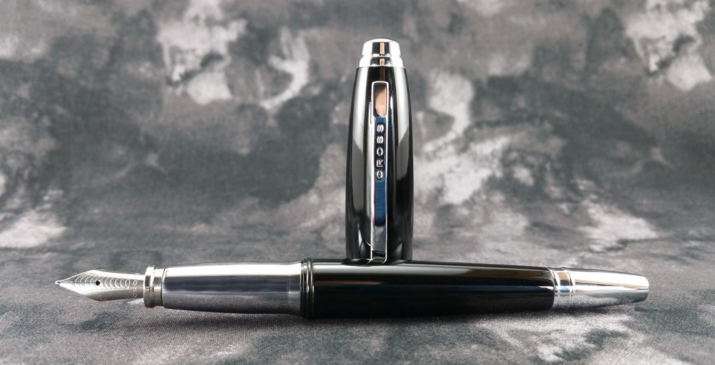The Cross Dubai Fountain Pen Uncapped with the pen laying down and the cap standing up behind it