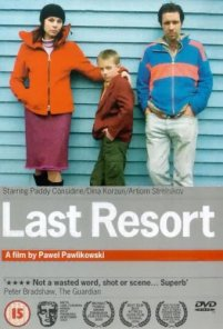 From left to right: Dina Korzun, Artyom Strelnikov and Paddy Considine  are standing against a blue panneled beach hut.The bottom third of the cover is a light grey background with the title Last resort in bold white text. Below are the awards that the film has won.