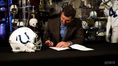 Andrew Luck signs the contract that makes him the NFL's best paid player.