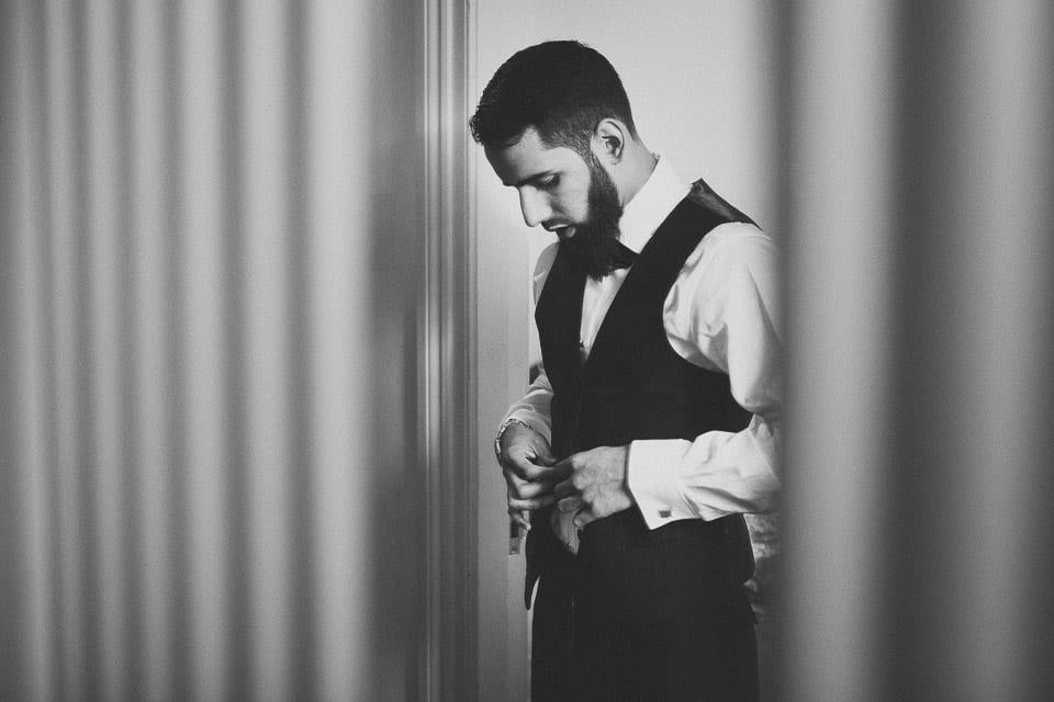 muslim groom doing up his waistcoat in the mirror