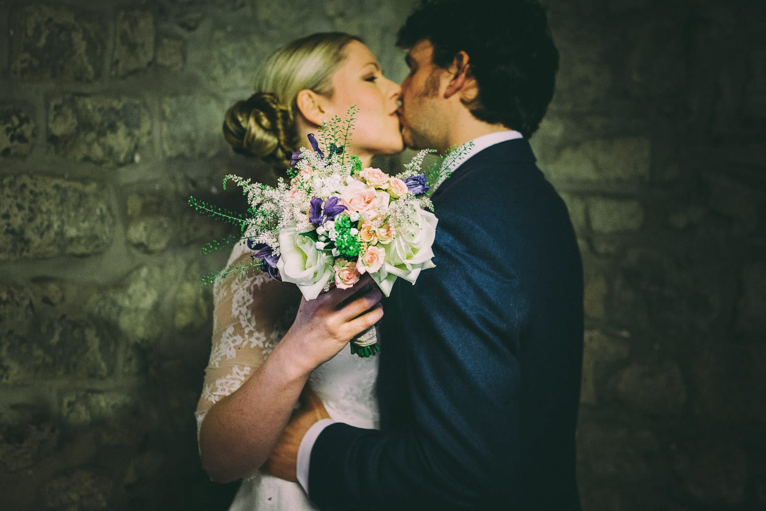 the bride and groom kiss in the church entrance