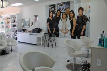 The sleek salon features a picture of the team. Owner Mericell Diaz is in the center and Skincare Specialist Andrea Kasa is behind her to the right.