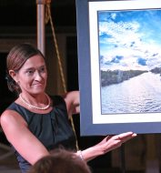 Karen Moore shows 'Riviera Canal Sunset' by Bob Slitzan. Later, Moore's own jewelry went up on the auction block.