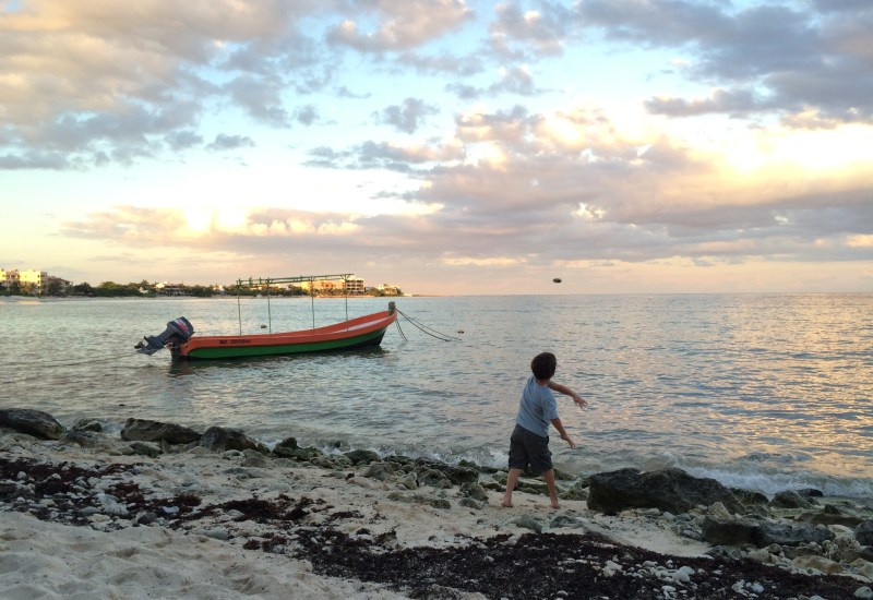 Sunset in Akumal. Most hotels and restaurants sweep away the drifts of seaweed that wash up on shore daily.