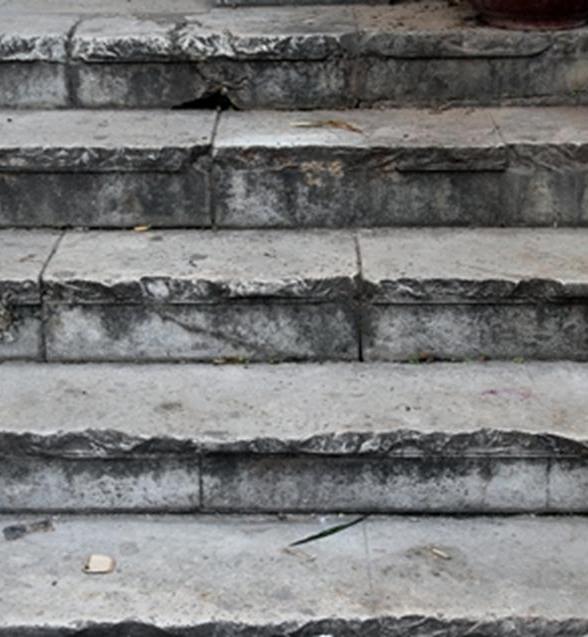 Bậc thang bằng đá cũng đã ố màu theo thời gian và nứt vỡ nham nhở.