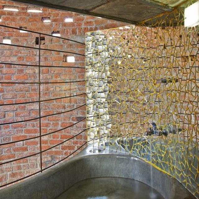 Công trình được lấy cảm hứng từ các tác phẩm của kiến trúc sư Laurie Baker, sử dụng các kỹ thuật xây gạch rat-trap bonds, mái vòm gạch, sàn filler, gạch Jalis, đồ nội thất cố định và vật liệu địa phương giúp làm giảm chi phí xây dựng từ thép, xi-măng, gạch và công nghệ thân thiện với môi trường.