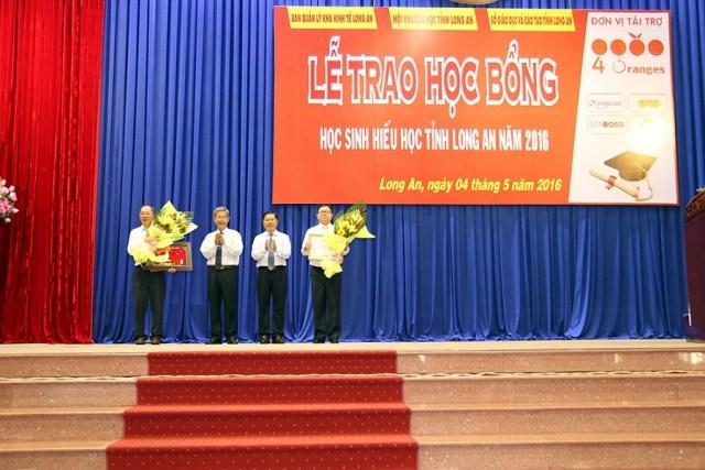Ông Phạm Thanh Phong-Chủ tịch Hội khuyến học tỉnh Long An cùng ông Lê Tấn Dũng-Phó chủ tịch UBND tỉnh Long An trao bằng khen cho phía nhà tài trợ công ty 4 Oranges.
