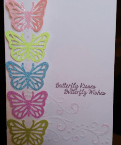 white card with swirled and glittered embossed design, five glittery butterflies lined up left side of cards, pink, lime, blue, fuchsia, green with message butterfly kisses, butterfly wishes