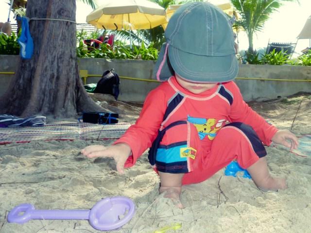 Smilla kollar in killen på stranden med likadan baddräkt men blå