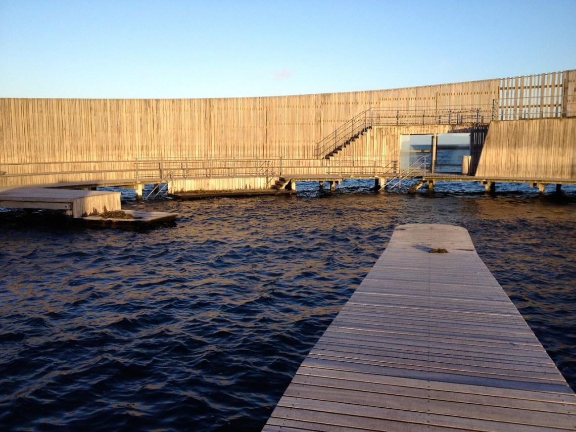 Het glazen scherm biedt bescherming tegen de harde zeewind, maar tegelijkertijd uitzicht op Zweden terwijl je je met zoet water afdoucht in de kleine cabines aan de randen.