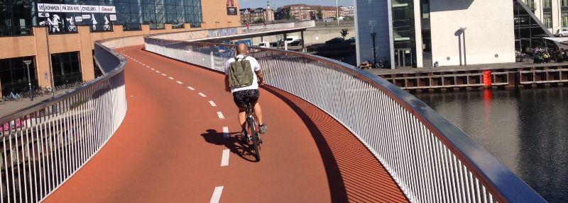 De fietsslang cirkelt zich een weg tussen de gebouwen door.