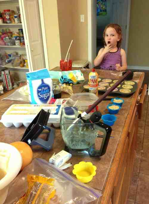 Little girl sitting at a messy counter, baking.