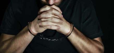 Man in handcuffs praying