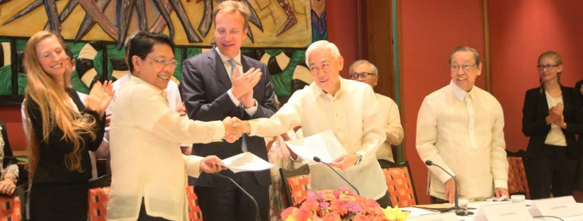 GRP Panel chair Silvestre BEllo III (left) and NDFP Panel chai Luis Jalandoni (right) shake hands as they exchange copies of their Joint Statement at the conclusion of the successful first round of talks in Oslo, Norway.