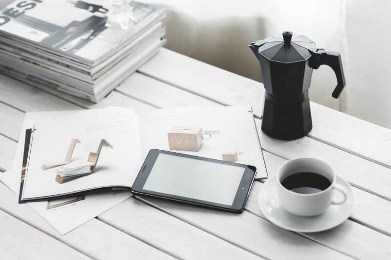 coffee-percolator-coffee-cup-digital-tablet-and-magazines-on-white-table (1)