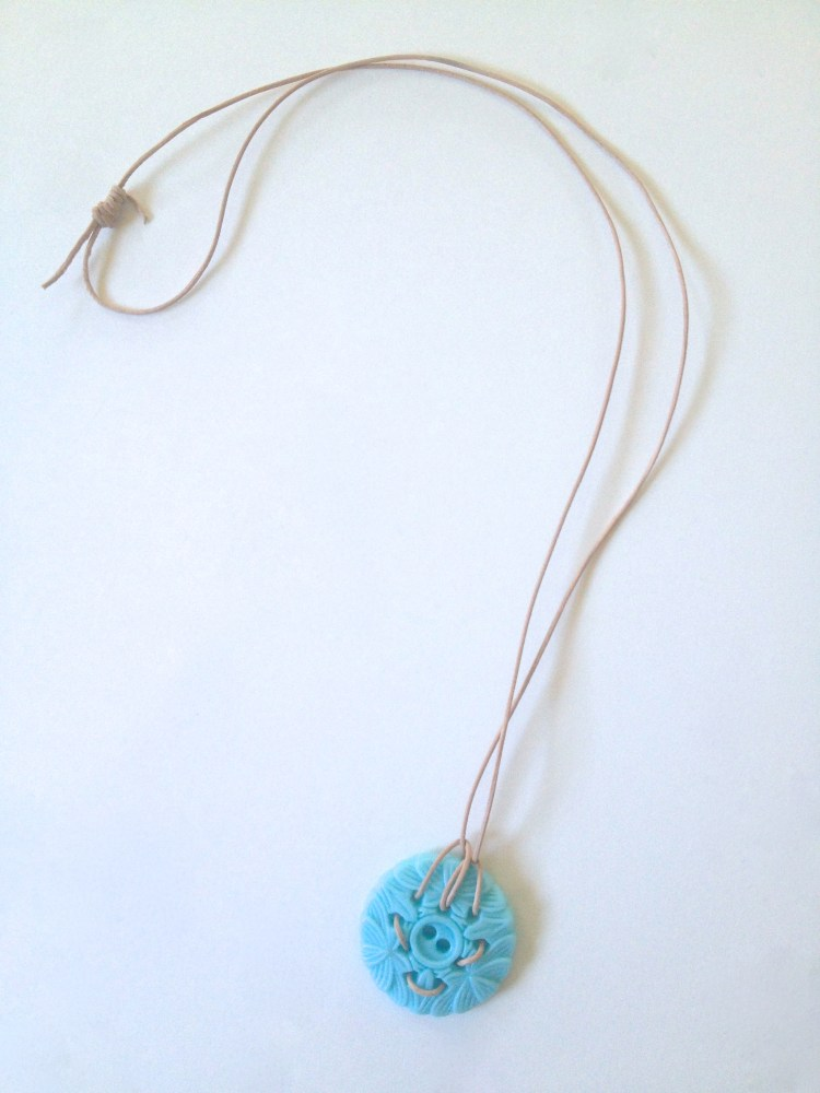 Decorative sticker button and natural leather cord.