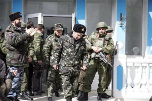 Ukrainian servicemen pass by armed men while leaving …