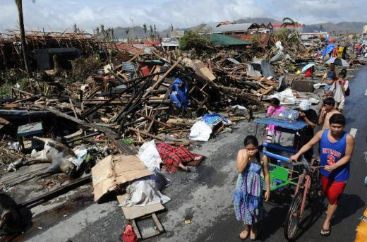 Residents walk past destroyed houses and dead bodies littered along a road in Tacloban, Philippines on November 10, 2013 after Super Typhoon Haiyan swept over the country