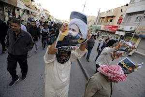 Protesters holding poster of Saudi Shi'ite cleric Nimr…