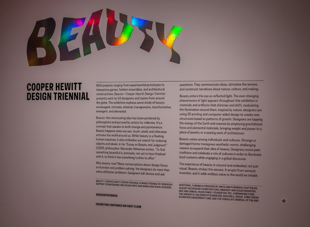 Triennial's wall text, with the collect icon in the lower-right corner