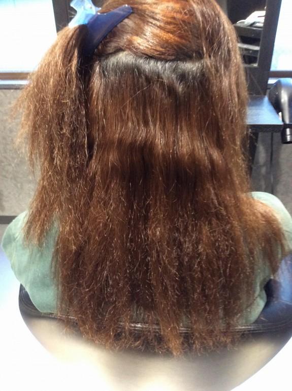 縮毛矯正を掛ける前のビフォー写真です。根元は癖が強く毛先がヂリヂリで髪の毛は非常に多い状態の画像です。