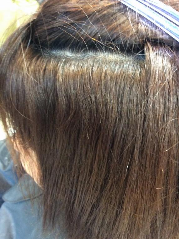 ブリーチした髪の毛のアップ画像です。上の部分を持ち上げて中が見え易くしています。髪の毛の長さは20センチくらいで毛先10センチはジリジリビビリ毛じょうたいです。根元には大きな癖が残っています。根元部分は色が抜け切れていなくて少し暗い色になってます。横から写真を撮りました。根元部分は色が黒に近いです。