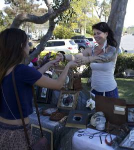 Silke Turner hands reporter Amarah Eden her hand-made body chain. (Photo by Niko LaBarbera)