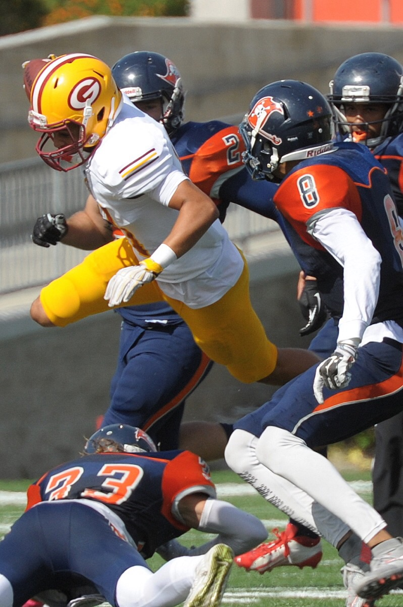 Sophomore wide receiver Zach Davis (No. 11, white) flys over multiple Orange Coast College defenders. Davis had two touchdown receptions in the game. (Cliff Robbins)