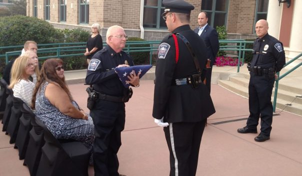 Retiring Chief George Kehl receives the American flag flying at the Police headquarters, from the department Color Guard