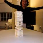 A Woman Pulls Off an Epic Jenga Move by Quickly Hitting Out the Bottom Brick Without Knocking Over the Tower