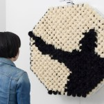 A Hypnotizing Anthropomorphic Mirror That Reflects Images With Black and Beige PomPoms