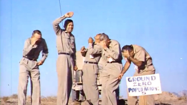 5 volunteers standing under an Aerial Nuclear Test