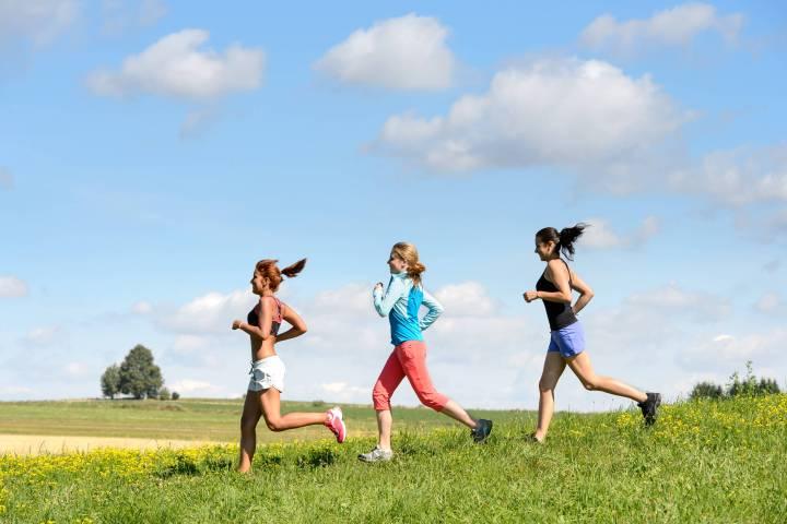 Female friends running downhill through sunny meadow summer sport