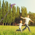 Dad and son running in meadow flying kite