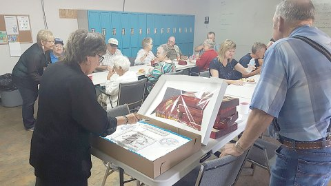 Long-time employee Debbie Aadland cuts the cake at an anniversary party for Commutron Industries, Ltd., at the company's office in Elbow on Sept. 2.