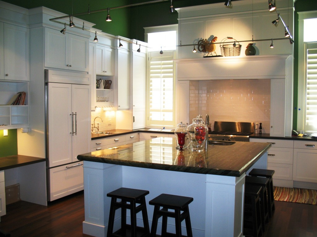 White kitchen cabinets with green granite counter tops.