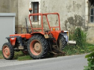 Tractor deliberately parked to hide demolition announcement of traditional Gessien farm buildings.