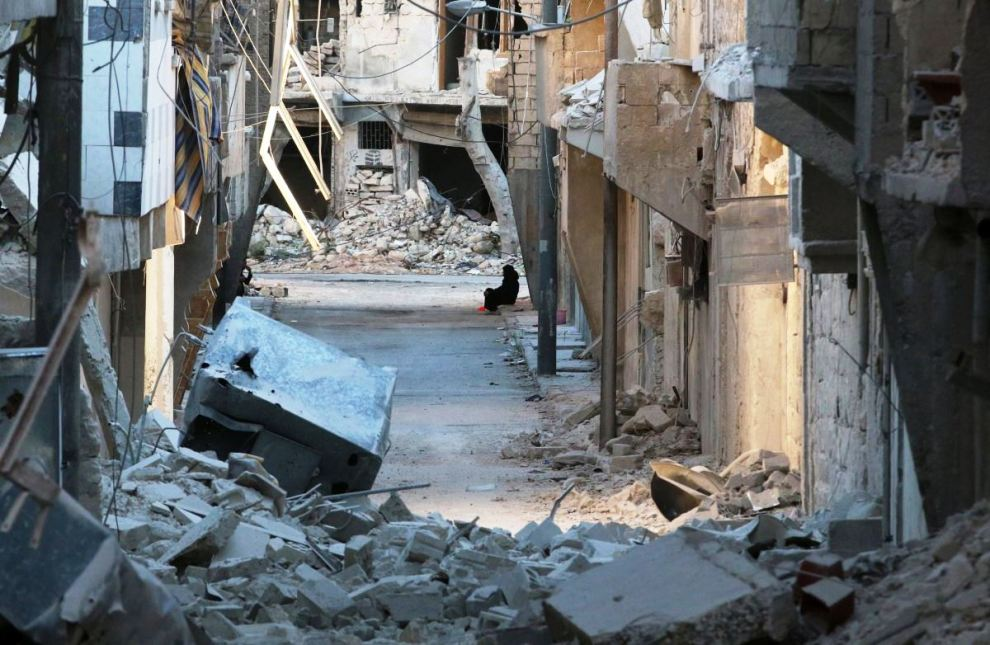 A woman sits amid damaged buildings in the rebel-held al-Myassar neighbourhood of Aleppo, Syria, September 27, 2016. REUTERS/Abdalrhman Ismail