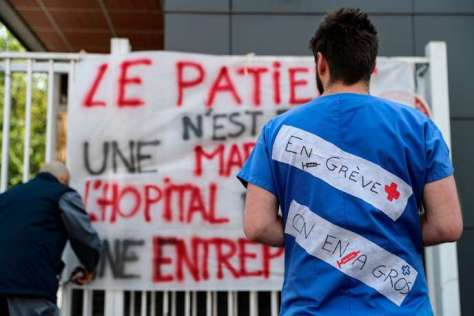 "An Emergency employees of French public hospital system AP-HP (Assistance publique-Hopitaux de Paris) wearing a message reading ""on strike"" stands in front of a banner reading ""The patient is not a merchandise"" as they protest against working conditions, at the entrance of the Pitie-Salpetriere Hospital in Paris on April 15, 2019. The two main unions denounce ""unbearable"" working conditions, while management promises reinforcements. The strike began in mid-March 2019 after a series of attacks at the Saint-Antoine hospital in the east of the capital. / AFP / KENZO TRIBOUILLARD"