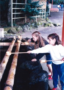 Amaree and Marissa getting holy water at a Shinto Shrine