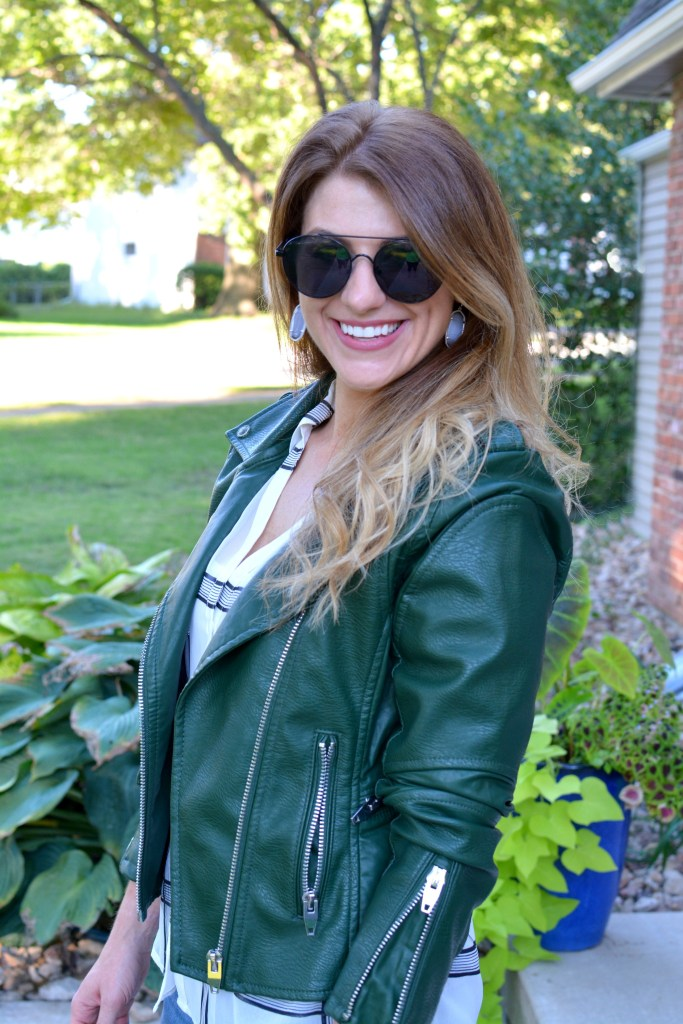 Ashley from LSR in a green leather jacket and a sheer windowpane blouse