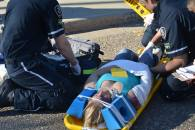 Paramedics check the vitals of a young woman involved in the collision and prepare her ti br transported to the nearest hospital.