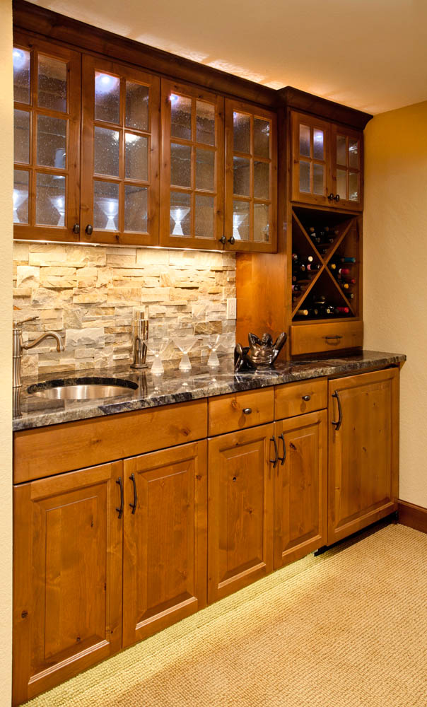 A modest wine rack with a sink fashioned in a basement