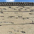 part of a house wall missing bricks.JPG